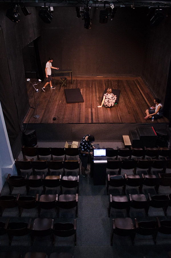 Top view of actors rehearsing on stage in front of an empty theater.